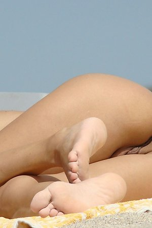 lovely young ladies loves to push the legs on a hot sand