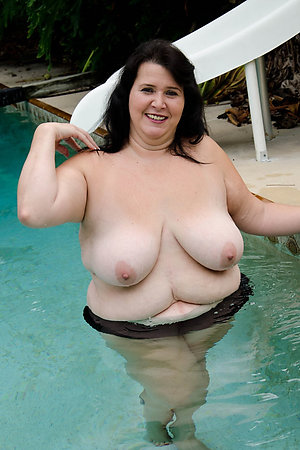 Fat mature nudist women swimming in a pool
